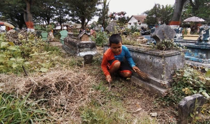 Seorang anak sedang membersihkan makam. (Foto:Azmy/Tugu Jatim)