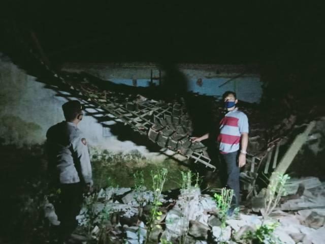 Kepala Desa (Kades) Ringinsari, Slamet Winari, saat menunjukkan beberapa bangunan yang roboh di desanya pasca diguncang gempa Malang M 6,1, Sabtu (10/4/2021) lalu. (Foto: Rizal Adhi Pratama/Tugu Malang/Tugu Jatim)