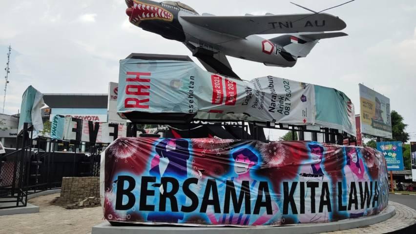 Monumen Pesawat di Jalan Seokarno Hatta, Kota Malang yang dipenuhi papan reklame dan akhirnya ditutup oleh spanduk. (Foto: Feni Yusnia/Tugu Malang/Tugu Jatim)