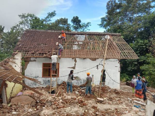 Warga bergotong-royong mengamankan atap yang masih bisa difungsikan di puing-puing rumah Mujiati. (Foto: M Sholeh/Tugu Malang/Tugu Jatim)