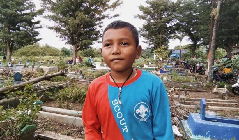 Dian Kurniawan (8), bocah pemburu rejeki di kuburan TPU Kutobedah, Kota Malang. (Foto: M Ulul Azmy/Tugu Malang/Tugu Jatim)