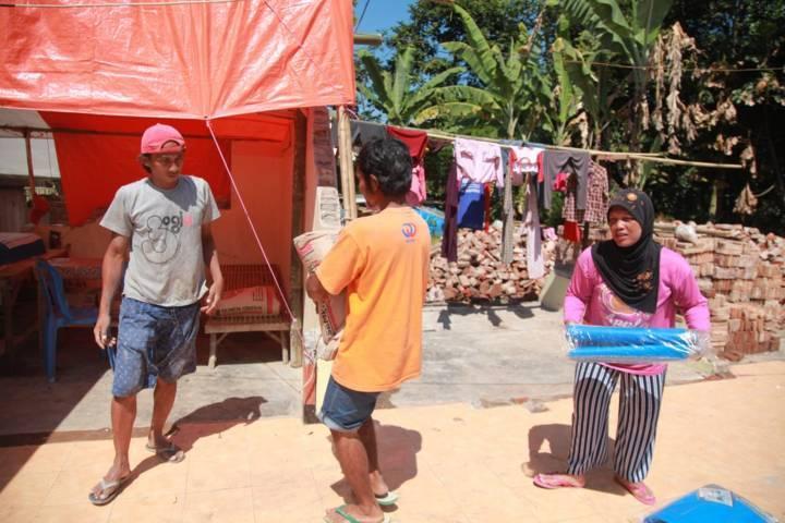 Warga turut membantu tim Tugu Media Group ketika menyalurkan bantuan pada korban gempa di Dampit, Malang, Selasa (27/4/2021). (Foto: Bayu Eka/Tugu Malang/Tugu Jatim)