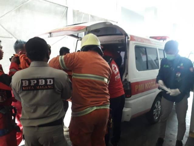 Petugas PMK, BPBD, dan TRC membawa korban ke mobil ambulans untuk dibawa ke rumah sakit. (Foto: Azmy/Tugu Jatim)