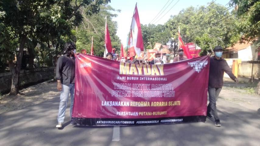Gerakan Mahasiswa Nasional Indonesia (GMNI) Universitas Negeri Surabaya (Unesa) dalam aksi Hari Buruh Nasional bersama serikat pekerja di depan Disnaker Provinsi Jatim, Sabtu (01/05/2021).(Foto: Rangga Aji/Tugu Jatim)