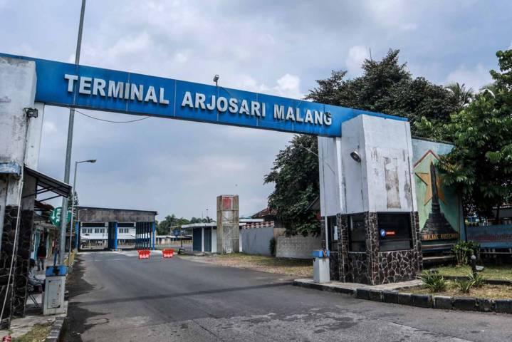 Tampak depan Terminal Arjosari Malang pada Kamis (6/5/2021) ini yang mulai sepi lantaran adanya peraturan larangan mudik. (Foto: Bayu Eka/Tugu Malang/Tugu Jatim)