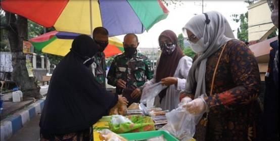 Ketua Persit Dini Nyarman memborong makanan dari pedagang saat Ramadhan. (Foto: Dok/Tugu Jatim)