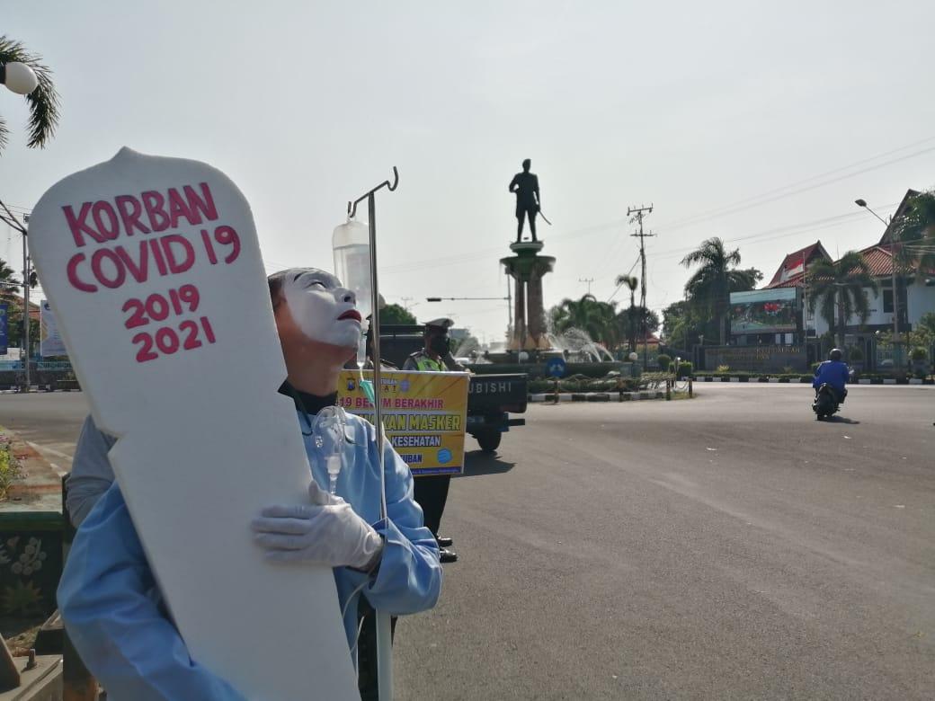 Petugas Polres Tuban melakukan aksi treatrikal untuk sosialisasi bahaya virus Covid-19. (Foto: Rochim/Tugu Jatim)