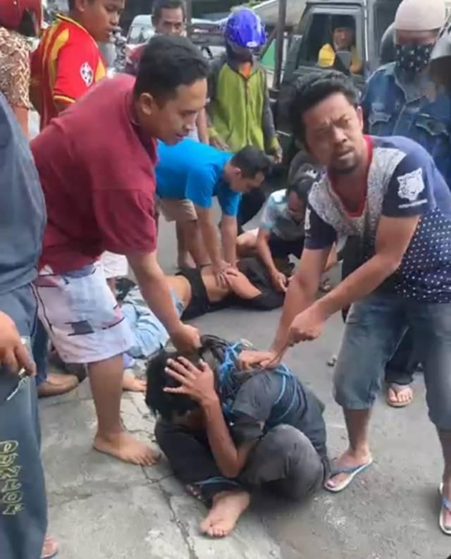 Pelaku pencurian burung di Jalan Teluk Grajakan, Kecamatan Blimbing, Kota Malang, diamuk massa karena diduga menusuk salah seorang warga Sabtu (29/05/2021). (Foto: Tangkapan layar/Azmy/Tugu Jatim)