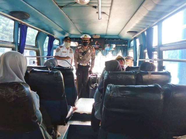 AKP Rizal Nugra Wijaya mengimbau kepada penumpang bus agar tetap jaga jarak dan melaksanakan protokol kesehatan. (Foto: Mila Arinda/Tugu Jatim)
