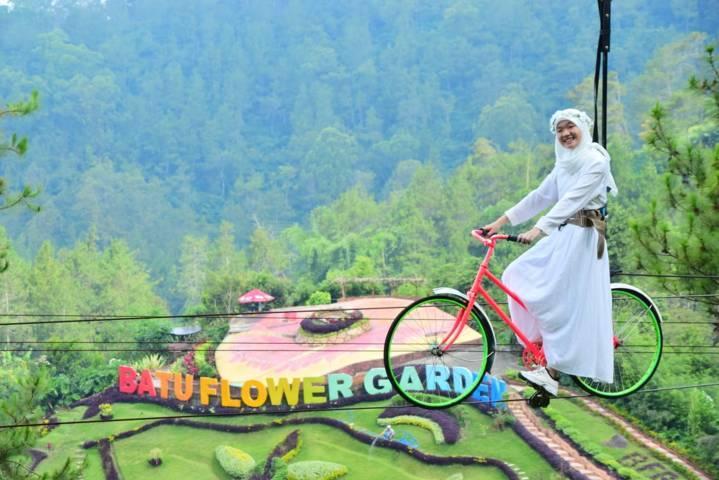 Wisatawan menikmati salah satu wahana yaitu gowes udara di Batu Flower Garden. (Foto: Batu Flower Garden/Tugu Jatim)