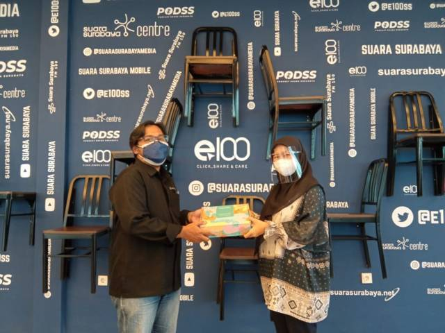 Dwi Wahyu Kurnia,Market Development Manager PTI Surabaya, memberikan cenderamata kepada Manajer Produksi Suara Surabaya Eddy Prasetyo. (Foto: Dimas Ari/Tugu Jatim)