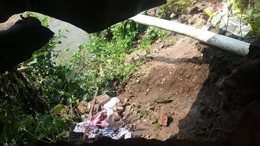 Tempat longsoran di bibir Sungai Metro. (Foto: Azmy/ Tugu Jatim)