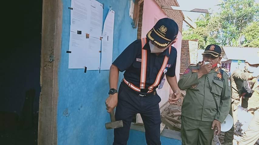 Deputi Eksekutif Vice President DAOP 8 Surabaya Mariyanto secara simbolis menghancurkan tembok bangunan, tanda penggusuran eks Lokalisasi Girun. (Foto: Rap/Tugu Jatim)