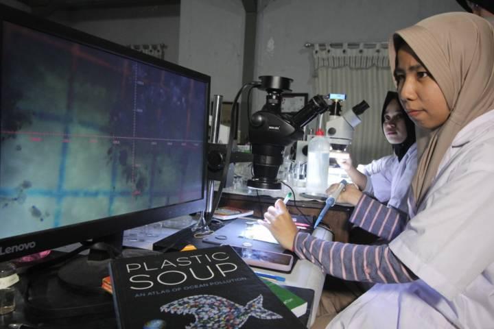 Mahasiswi Jurusan Biologi UIN Sunan Ampel Surabaya menunjukkan bahwa ada kontaminasi mikroplastik pada biota air di pesisir kawasan Sidoarjo. (Foto: Ecoton/Tugu Jatim)