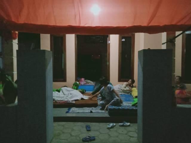 Takut terjadi gempa susulan, Nur Halimah (piyama warna biru), dan keluarganya tidur di teras rumah. (Foto: Rap/Tugu Jatim)