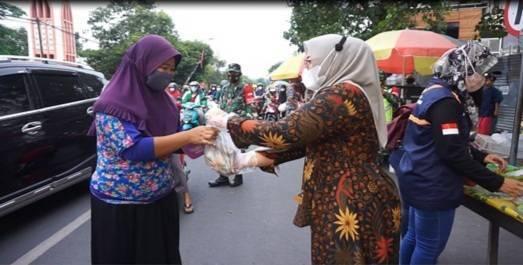 Ketua Persit Dini Nyarman memberikan makanan untuk warga Pasuruan. (Foto: Dok/Tugu Jatim)