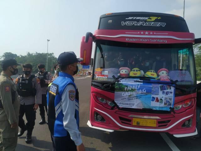 Bus yang membawa rombongan wisatawan asal Gresik yang dicegat petugas di pintu Exit Tol Madyopuro, Kota Malang, Sabtu (22/05/2021). (Foto:Istimewa/Tugu Jatim)
