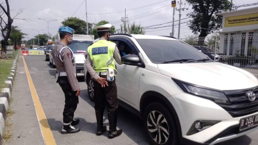 Petugas kepolisian mengecek dan menempeli kendaraan yang melintas yang menuju arah Surabaya maupun Madura.(Foto: Rangga Aji/Tugu Jatim)
