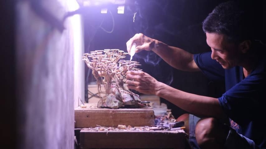 Nanang Subandi tampak konsentrasi untuk membuat bonsai aquatic-nya. (Foto: Zamzuri/Tugu Jatim)