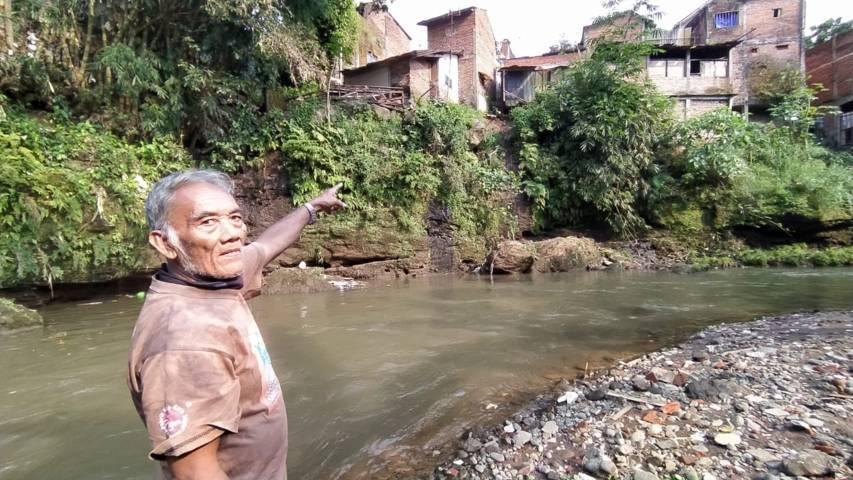 Misdi, 68, warga yang menunjukkan lokasi tanah bangunan toilet di bibir Sungai Metro yang longsor pada Sabtu (01/05/2021). (Foto: Azmy/ Tugu Jatim)