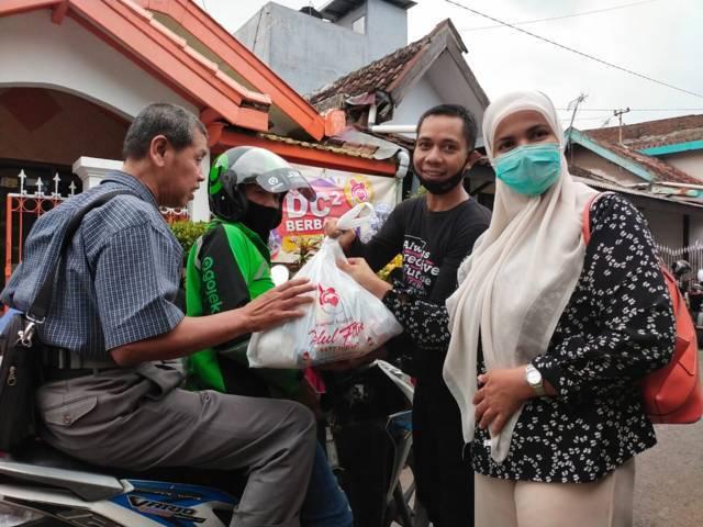 Istri dr Tandya, Aminah Najmah memberikan paket sembako kepada salah satu difabel tunanetra, Jumat (7/5/2021). (Foto: Dokumen/Tugu Jatim)