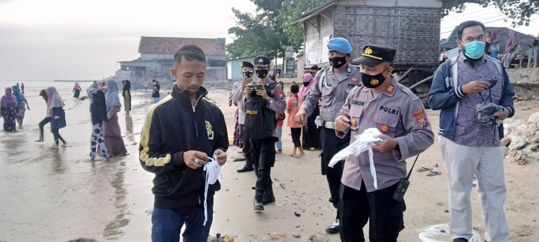 Ingin mencegah persebaran Covid-19, petugas Polsek Palang membagikan 300 masker kepada warga. (Foto: Rochim/Tugu Jatim)