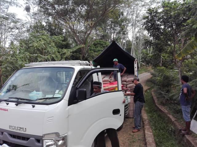 Material bangunan dari Tugu Media Peduli X Bakti BCA dimuat ke mobil buah milik warga. (Foto: Dicky Hanafi/Tugu Jatim)