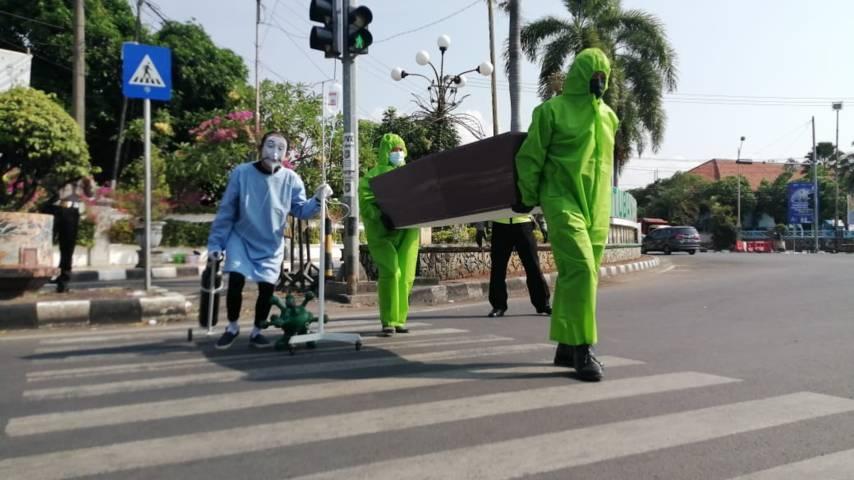 Aksi treatrikal untuk sosialisasi bahaya virus Covid-19 dengan membawa peti mati hingga tabung oksigen sendiri. (Foto: Rochim/Tugu Jatim)