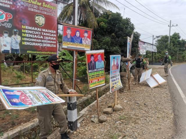 Penertiban spanduk dan reklame hajatan yang dilakukan oleh Satpol PP di Kecamatan Munjungan, Kabupaten Trenggalek, Rabu (26/5/2021). (Foto: M Zamzuri/Tugu Jatim)