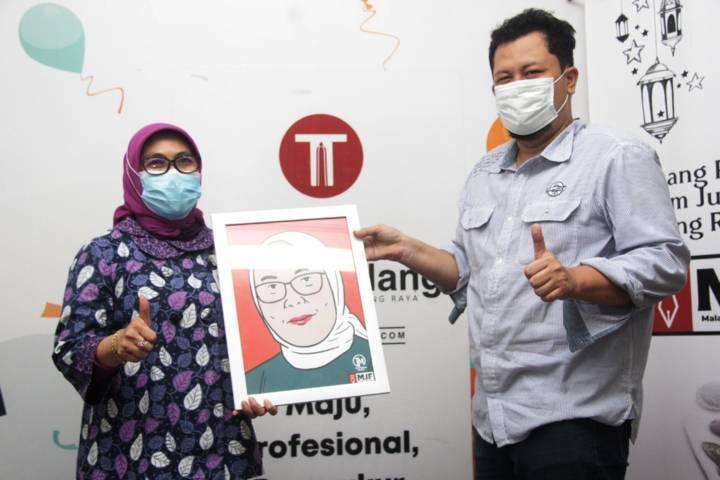 Pemimpin BNI Kantor Wilayah 18 Beby Lolita Indriani mendapat cindermata dari CEO Tugu Media Group, Irham Thoriq. (Foto: Rubianto/Tugu Malang/Tugu Jatim)