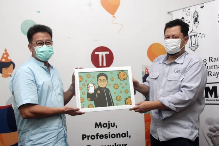 Direktur PT Agro Mitra Alimentare (AMA), Ge Recta Geson menerima kenang-kenangan dari CEO Tugu Media Group, Irham Thoriq/ (Foto: Rubianto/Tugu Malang/Tugu Jatim)