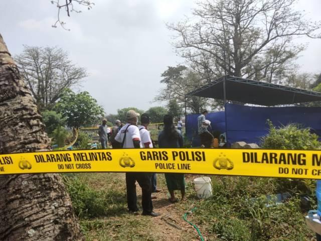 Garis polisi terlihat melintang saat proses pembongkaran makam di TPU Sukorejo, Blimbing, Kota Malang, Kamis (20/5/2021). Makam jenazah perempuan yang ditemukan tak bernyawa di Bendungan Sengguruh, Malang tersebut dibongkar lantaran pihak keluarga merasa kematian yang tak wajar. (Foto: Istimewa)