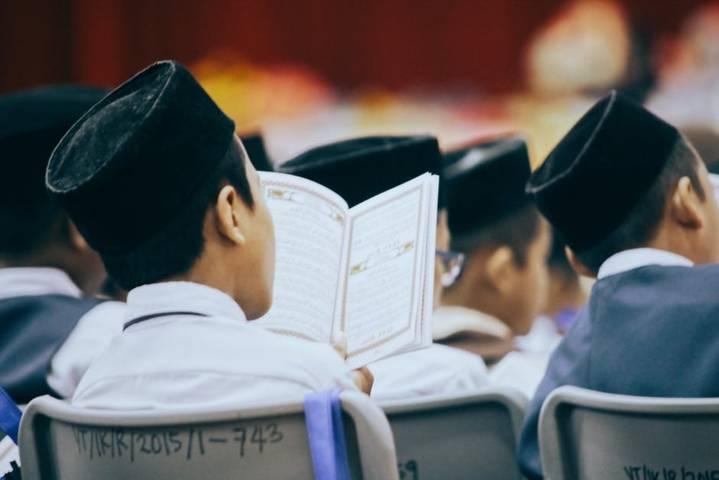 Ilustrasi santri sedang mengaji Al-Qur'an. (Foto: Pexels) larangan mudik