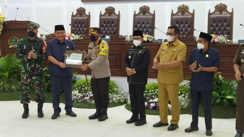 Ketua DPRD I Made Riandiana Kartika menyerahkan kenang-kenang secara langsung kepada Kombes Pol Leonardus Simarmata. (Foto: Azmy/Tugu Jatim)