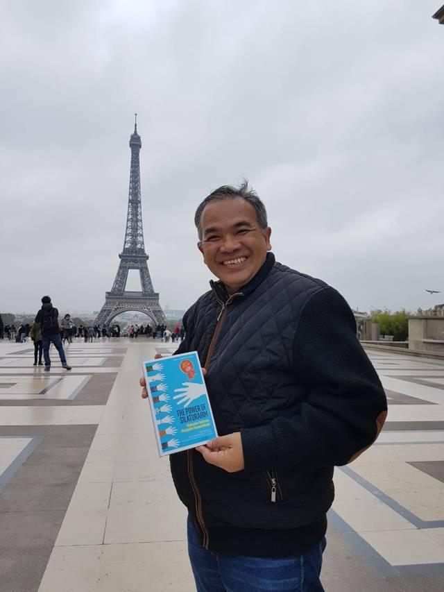 Pakar Komunikasi dan Motivator Nasional Dr Aqua Dwipayana saat berada di Paris dengan membawa buku karyanya. (Foto: Dokumen/Tugu Jatim)