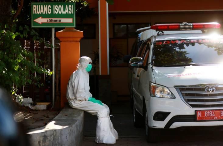 Salah satu petugas PSC 119 Dinkes Kota Malang yang tampak siaga di depan mobil ambulans. (Foto: Rubianto/Tugu Jatim)