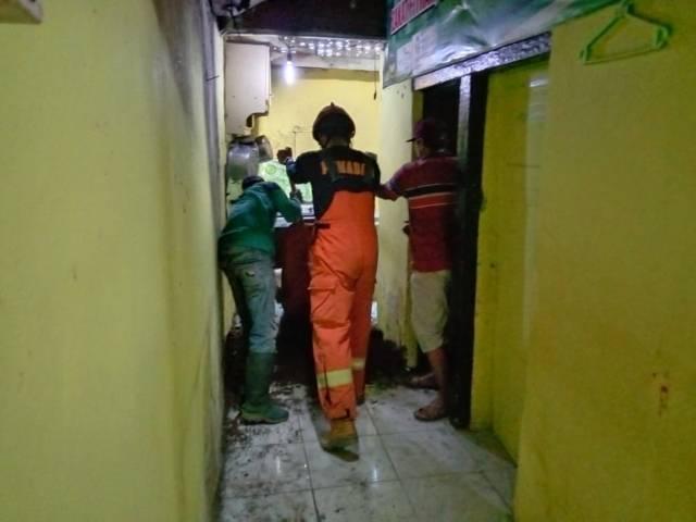 Petugas menguruk lubang rumah warga akibat tanah ambrol di Kota Batu. (Foto: Sholeh/Tugu Jatim)