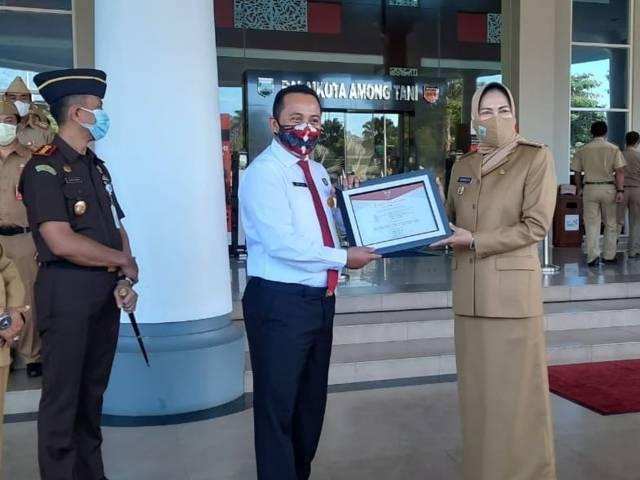 Kasi Datun Kejari Batu Muhammad Bayanullah menerima piagam penghargaan dari Wali Kota Batu Dewanti Rumpoko. (Foto: Sholeh/Tugu Jatim)