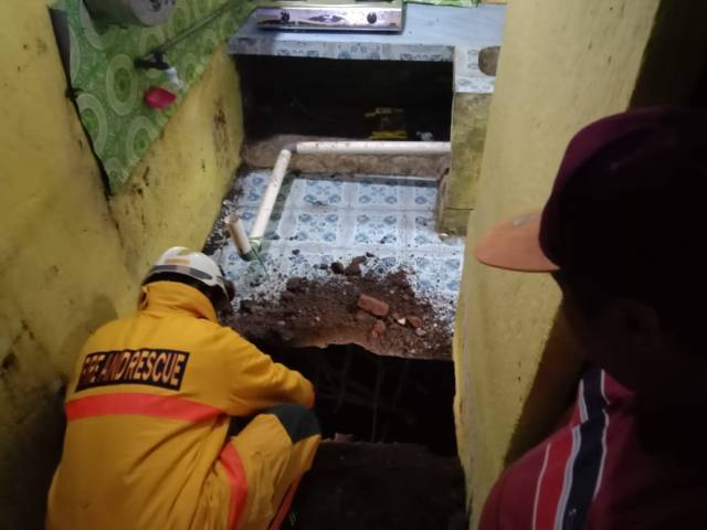 Petugas melihat kondisi rumah warga yang berlubang akibat tanah ambrol. (Foto: Sholeh/Tugu Jatim)