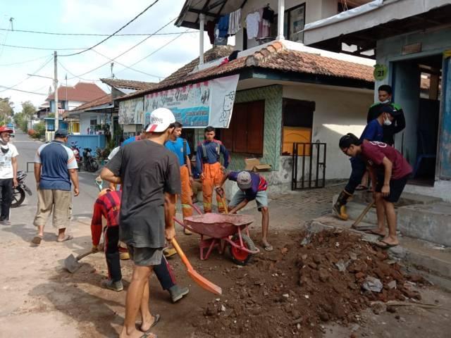 Petugas dibantu warga menguruk lubang rumah warga Kota Batu yang ambrol. (Foto: Sholeh/Tugu Jatim)