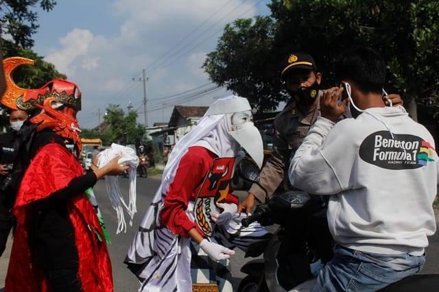 Kapolsek Puncu Polres Kediri bersama siswa SMAN 1 Puncu yang mengenakan kostum burung garuda membagikan masker kepada para pengguna jalan, Senin (31/5/2021) kemarin. (Foto: Rino Hayyu/Tugu Jatim) hari lahir pancasila