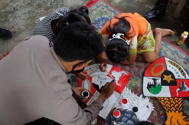 AKP Bowo Wicaksono, Kapolsek Puncu saat mendangi anak-anak untuk melukis burung garuda Pancasila. (Foto: Rino Hayyu/Tugu Jatim)
