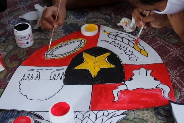 Simbol sila-sila yang berada di dada burung garuda di lambang Garuda Pancasila tengah dilukis dan diwarnai satu-satu oleh anak-anak dari Desa Gadungan, Kediri. (Foto: Rino Hayyu/Tugu Jatim)