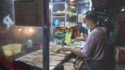 Sahroni, penjual Burger Fantasy saat melayani pesanan pembeli. (Foto: Feni Yusnia/Tugu Jatim)