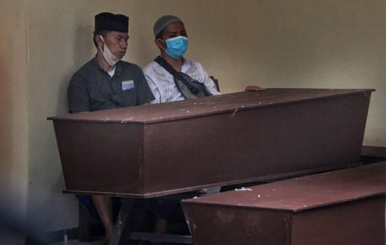 Keluarga jenazah tampak menunggu di hadapan peti mati keluarganya yang meninggal akibat terpapar Covid-19. (Foto: Rubainto/Tugu Malang/Tugu Jatim)