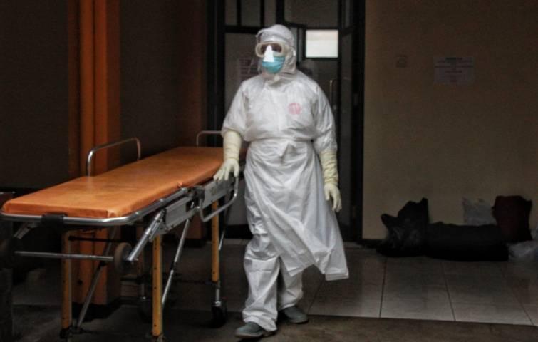Petugas tengah mempersiapkan jenazah sebelum diberangkatkan untuk dimakamkan sesuai prosedur pemakaman Covid-19. (Foto: Rubianto/Tugu Malang/Tugu Jatim)