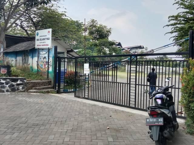 Situasi gerbang pintu masuk SMA SPI yang foundernya dilaporkan atas dugaan kekerasan seksual. (Foto: M Sholeh/Tugu Jatim)