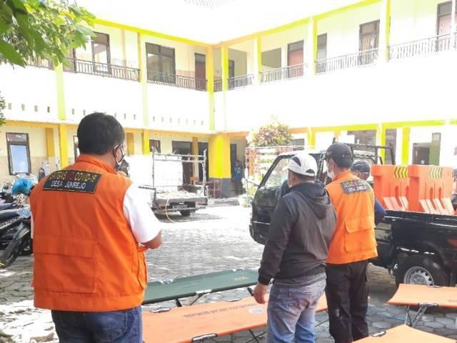 Warga Desa Junrejo gotong royong mendirikan shelter mandiri di SMP Diponegoro Junrejo Kota Batu. (Foto: Sholeh/Tugu Jatim)