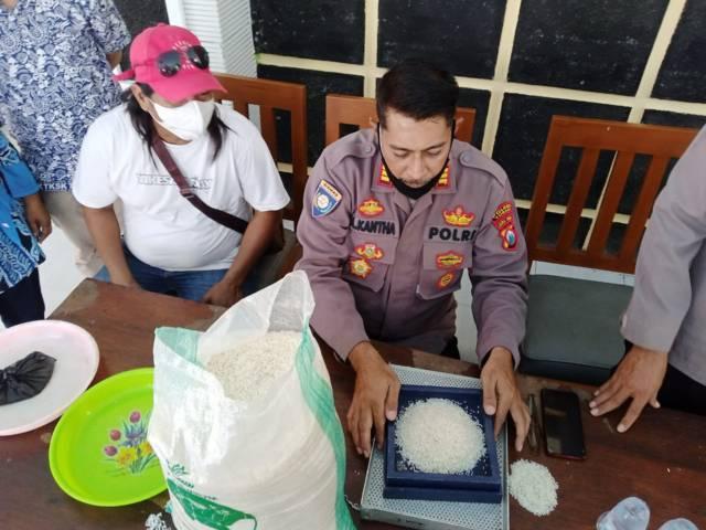 Kasat Binmas Polres Tuban AKP Ali Kanta mengecek kualitas beras BPNT di Kecamatan Soko, Kamis (22/07/2021). (Foto: Rochim/Tugu Jatim)
