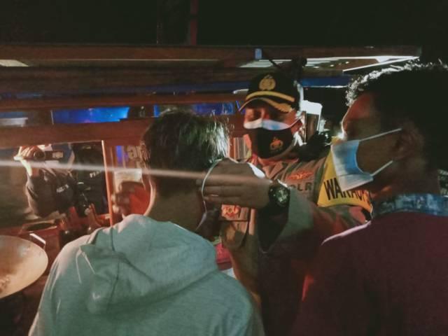 Wakapolres Malang Kompol Himawan Setiawan memakaikan masker kepada pedagang nasi goreng saat patroli malam, Jumat (23/07/2021). (Foto: Rizal Adhi/Tugu Jatim)